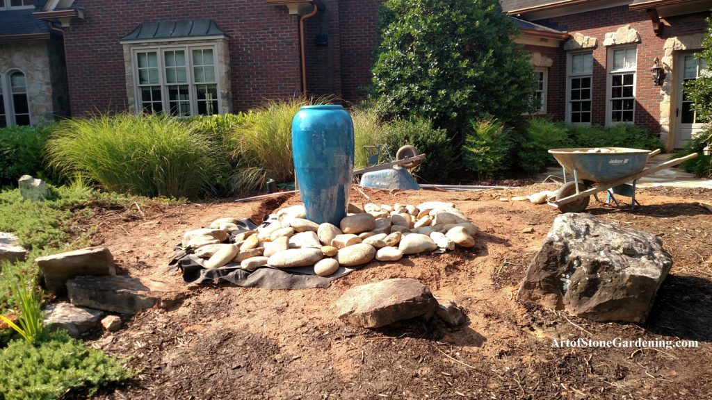 Installing rocks around fountain