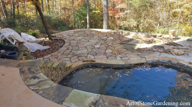 New stone patio surrounding pool