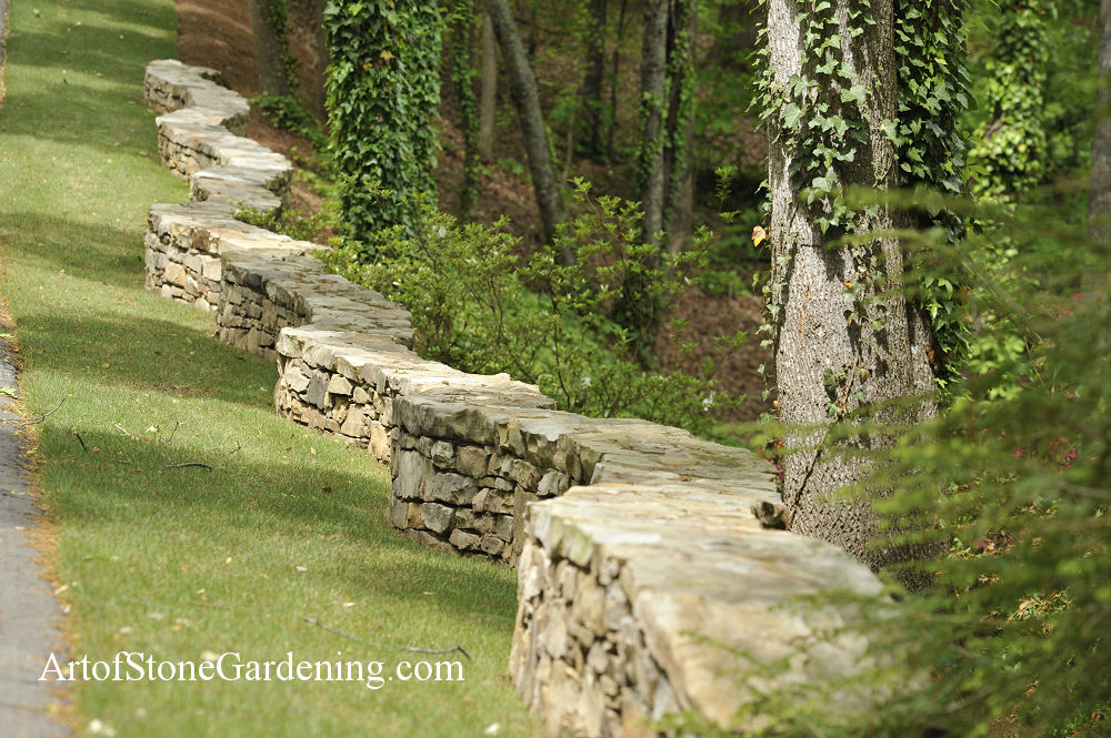 freestanding mortared wall separates mowed and natural areas